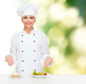 Smiling female chef with salad and cake on plates — Stockfoto