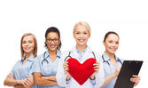 Smiling female doctor and nurses with red heart — Stock Photo