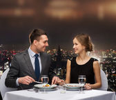 Smiling couple eating main course at restaurant — Stockfoto