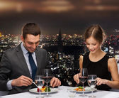 Smiling couple eating main course at restaurant — Zdjęcie stockowe