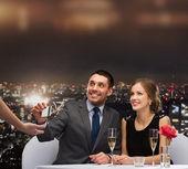 Couple souriant payer pour le dîner avec carte de crédit — Photo
