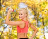 Jonge, sportieve vrouw met lichte dumbbell — Stockfoto