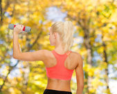Joven deportiva con luz con mancuernas — Foto de Stock