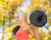 Smiling sporty woman exercising with barbell — Stock Photo