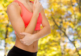 Sporty woman with pain in elbow — Stock Photo