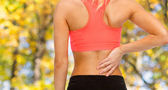Close up of sporty woman touching her back — Stock Photo