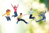 Group of smiling teenagers jumping in air — Stock Photo