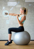 Smiling woman with dumbbells and exercise ball — Stock Photo