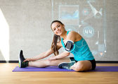 Smiling woman stretching leg on mat in gym — Stock Photo
