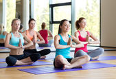 Smiling women meditating on mat in gym — Stock Photo