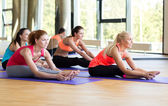 Group of smiling women stretching in gym — Stock Photo