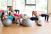 Skupina usmívající se žen s míčky cvičení v tělocvičně — Stock fotografie