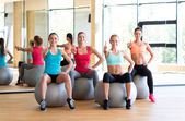 Group of smiling women showing thumbs up in gym — Stock Photo