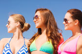 Group of smiling young women on beach — Stock Photo