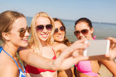 Group of smiling women making selfie on beach — Stock Photo