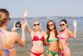 Group of smiling women photographing on beach — Stock Photo