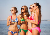 Group of smiling women eating ice cream on beach — Stockfoto