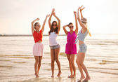 Group of smiling women dancing on beach — Stock Photo