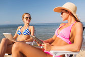 Smiling women with tablets pc computers on beach — Stock Photo