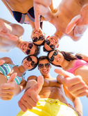Smiling friends showing thumbs up in circle — Foto Stock