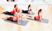 Group of smiling women stretching on mats in gym — Stock Photo