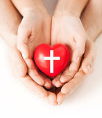 Couple hands holding heart with cross symbol — Stock Photo