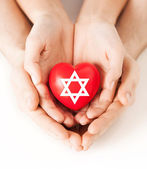 Couple hands holding heart with star of david — Stock Photo