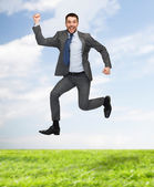 Smiling happy businessman jumping — Stock Photo