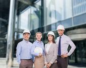 Group of smiling businessmen in white helmets — Stock Photo