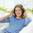 Smiling young girl in headphones at home — Stock Photo #51613105