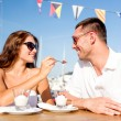 Smiling couple eating dessert at cafe — Stock Photo #51618183