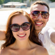 Smiling couple wearing sunglasses making selfie — Stock Photo #51618625