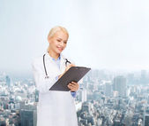 Smiling female doctor with clipboard — Stock Photo