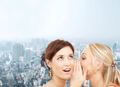 Two smiling women whispering gossip — Stock Photo