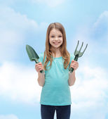 Smiling little girl with rake and scoop — Stock Photo