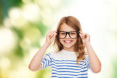 Smiling cute little girl with black eyeglasses — Stock Photo