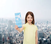 Smiling little girl with airplane ticket — Photo