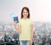 Smiling little girl with ticket and passport — Stock Photo