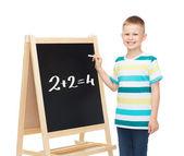 Smiling little boy with blank blackboard — Stock Photo