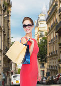 Smiling woman in red dress with shopping bags — Stock Photo