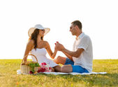 Smiling couple with small red gift box on picnic — Stock Photo