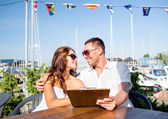 Smiling couple with menu at cafe — Stock Photo