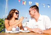 Smiling couple eating dessert at cafe — Stock Photo