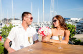 Smiling couple with bunch and champagne at cafe — Stock Photo
