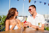 Smiling couple with champagne and gift at cafe — Stock Photo