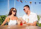 улыбаясь пара с шампанским и подарок в кафе — Стоковое фото