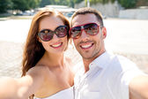 Smiling couple wearing sunglasses making selfie — Stock Photo