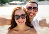 Smiling couple wearing sunglasses making selfie — Stok fotoğraf