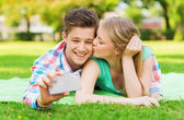 Smiling couple making selfie and kissing in park — Stock Photo
