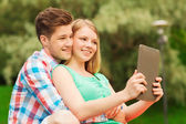 Smiling couple with tablet pc making selfie — Stock Photo
